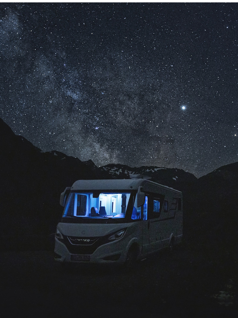 Class B Motorhome RV sits at campsite at night under starry sky