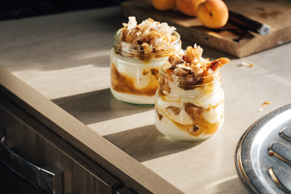 Clear glass jars layered with creamy, white yogurt, golden apricot sauce and toasted coconut flakes.