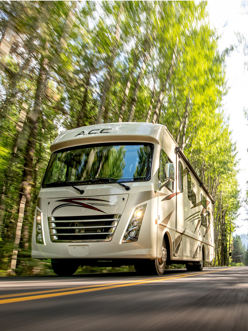 Class A RV drives on the road through wooded area