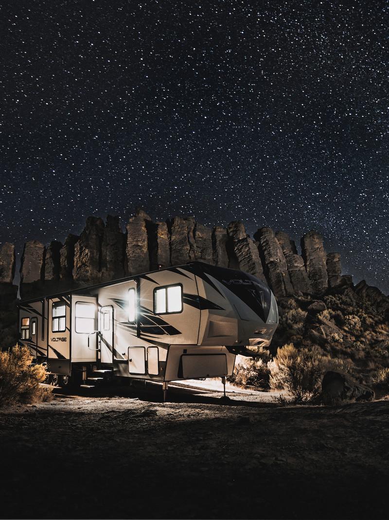 fifth-wheel travel trailer RV underneath dark starry sky at night