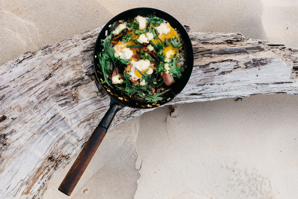 A cast iron skilled filled with cooked greens, bacon and eggs, balanced on a piece of driftwood on the beach.