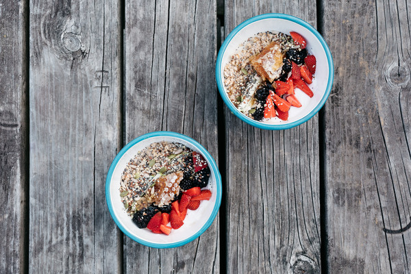 White bowls with a sky-blue rim sitting on a gray, aged wood picnic table. The bowls hold servings of overnight oats topped with colorful stripes of berries, chia seeds and honeycomb.