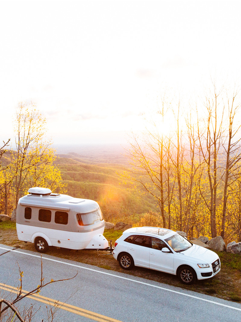 Lightweight Travel Trailer pulled by small SUV pulled over next to changing fall leaves