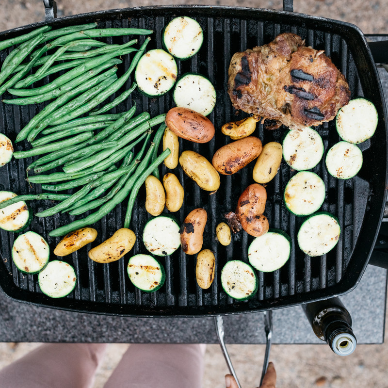 Aerial shot of green beans, potatoes, vegetables, and pork on a grill.