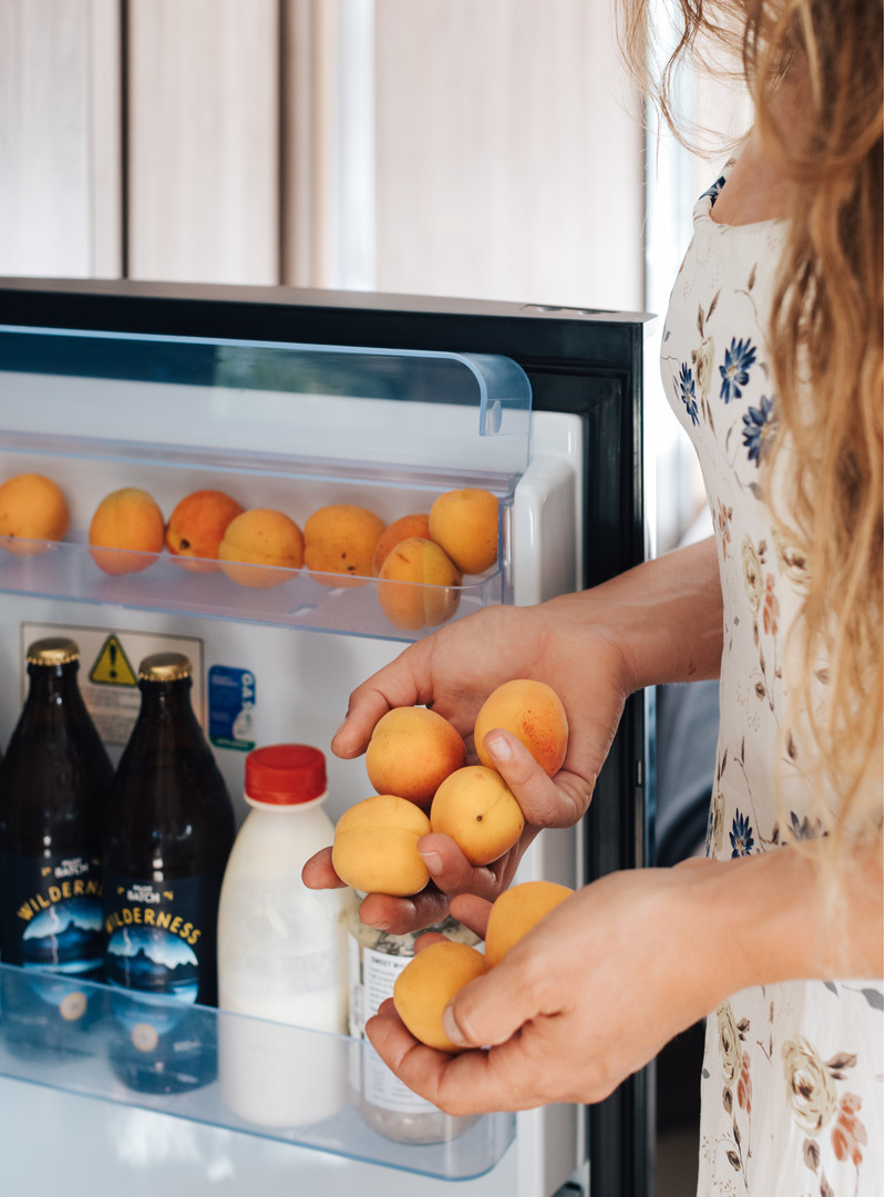 A close shot of a woman standing with the refrigerator door open. Her hands and the door are filled with fresh apricots.