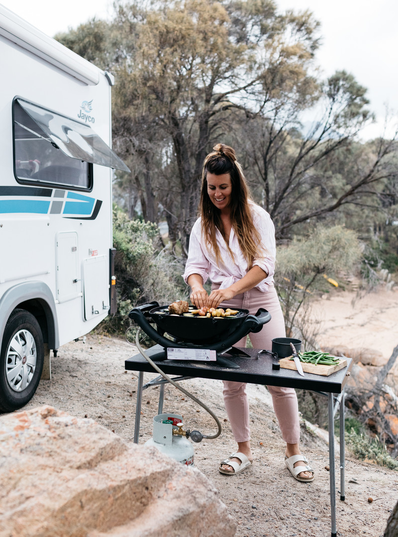 Sarah Glover grilling outside Jayco Class C motorhome.