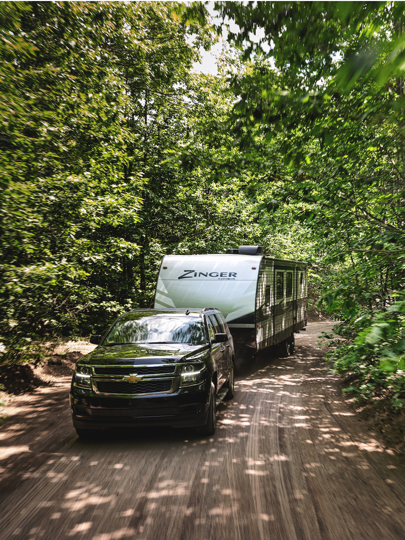 Travel Trailer RV pulled by SUV on dirt road through the woods