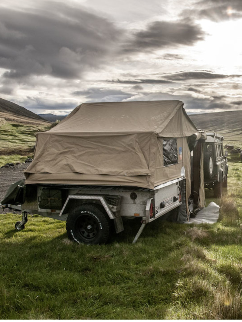 Expandable pop-up trailer sits in a field of green